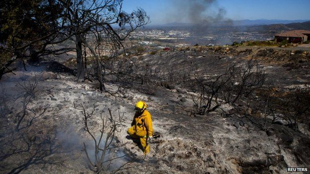 A fire fighter put out embers in San Marcos, California, on 15 May 2014