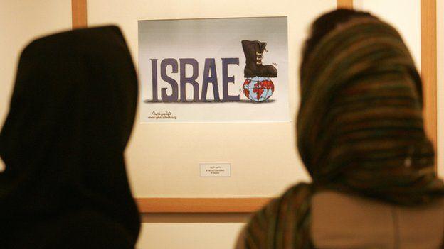 Iranian women look at anti-Israel cartoon in Tehran (file photo)