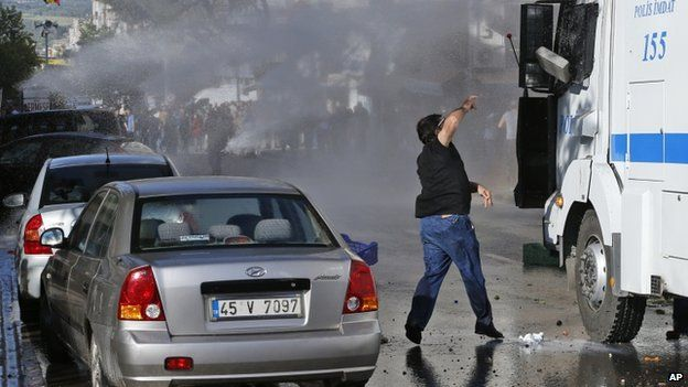An anti-government protester throws a stone at a police water canon as it is used against protesters during clashes with police in Soma