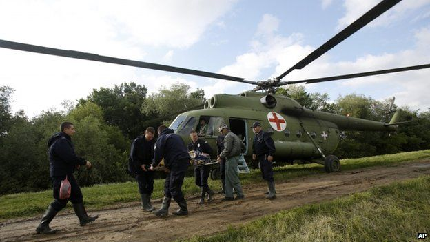 Serbian police officers carry an old woman from a military helicopter during evacuation from Obrenovac, some 30km (18 miles) south-west of Belgrade