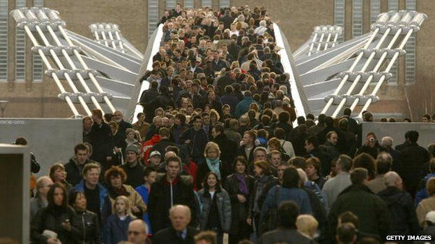 File photo: Thousands of people cross the Millennium Bridge for the first time after it reopens, 22 February 2002