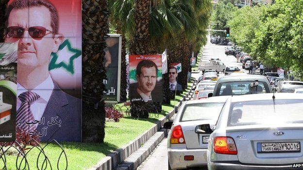 Syrians drive past election campaign posters bearing portraits of President Bashar al-Assad in Damascus - 18 May 2014