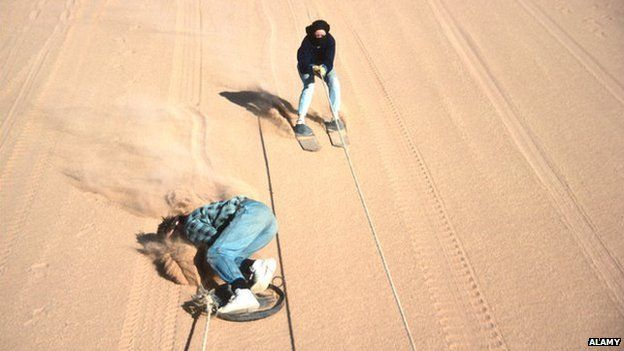 Tourists sand skiing in Namibia