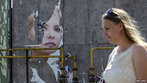 A woman and her daughter walk past a torn poster of Ukrainian politician and presidential candidate Yulia Tymoshenko in Luhansk, eastern Ukraine, May 16