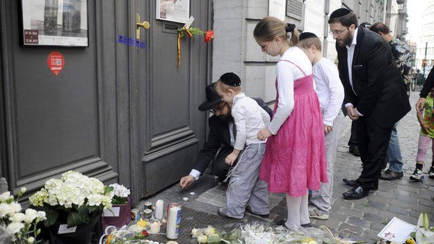 A family lights candles at the Jewish Museum, site of a shooting in central Brussels on 25 May 2014.
