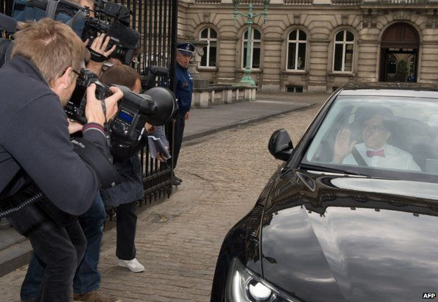 Prime Minister Elio Di Rupo waves as he leaves the Royal Palace in Brussels