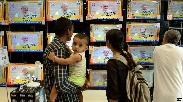 """Residents watch a bank of televisions featuring images of Narendra Modi taking his oath as India""""s Prime Minister in New Delhi at a multi brand electronic showroom in Mumbai on on May 26, 2014"""