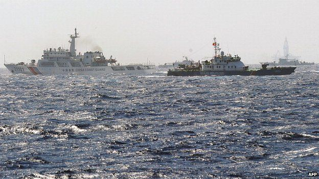 This picture taken from a Vietnam Coast Guard ship on 14 May shows a Vietnam Coast Guard ship (2nd R, dark blue) trying to make way amongst several China Coast Guard ships near to the site of a Chinese drilling oil rig (R, background) being installed at the disputed water in the South China Sea off Vietnam's central coast.