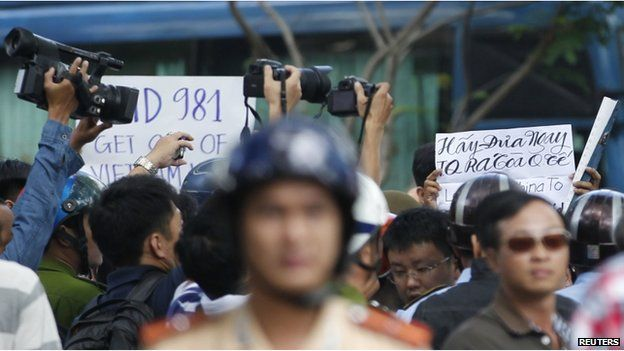 """Police and security personnel film protesters holding placards which read, """"Haiyang 981 oil rig get out of Vietnam (L)"""" and """"Take China to the international court"""" (R) as they march during an anti-China protest in Vietnam's southern Ho Chi Minh city May 18, 2014. Vietnam flooded major cities with police to avert anti-China protests on Sunday in the wake of rare and deadly rioting in industrial parks that deepened a tense standoff with Beijing over sovereignty in the South China Sea. Several arrests were made in the capital Hanoi and commercial hub Ho Chi Minh City within minutes of groups trying to start protests, according to witnesses, as Vietnam's communist rulers stuck to their vow to thwart any repeat of last week's violence in three provinces in the south and centre"""