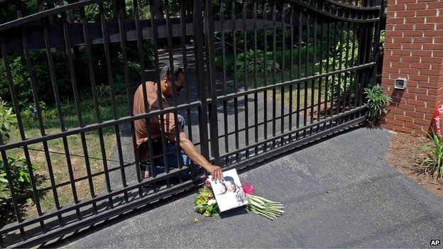 Groundskeeper and security guard for Maya Angelou, James Samuels, retrieves flowers left outside her home in Winston-Salem, North Carolina (28 May)
