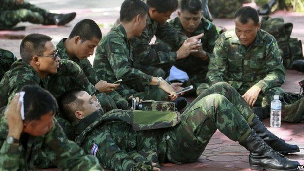 Thai soldiers rest on the ground at police headquarters after being deployed to prevent an anti-coup demonstrations in Bangkok, 1 June 2014