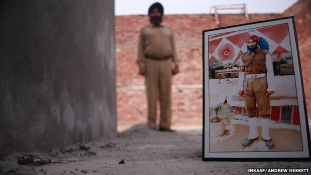 Satwant Singh Manak with a picture of himself in his uniform