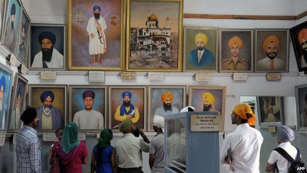 Visitors look at photographs of slain Sikh fighters, killed during Operation Blue Star in 1984, at a museum inside the Golden Temple complex