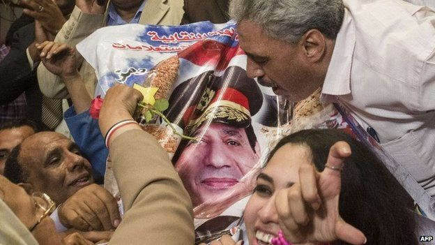 Egyptian journalists and officials kiss a picture of Abdul Fattah al-Sisi after he is declared the new president (3 June 2014)