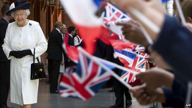 School children waving union jacks as the Queen walks past