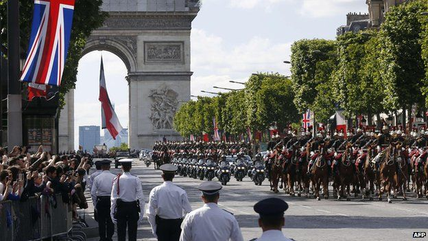 Motorcycle policemen escort the car carrying the Queen and French President Francois Hollande