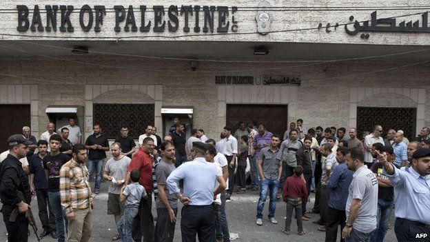 Hamas security forces stand guard as employees paid by the Palestinian Authority wait to receive their salaries outside a closed bank after a scuffle with employees appointed by Hamas since 2007, in Gaza City on June 5,