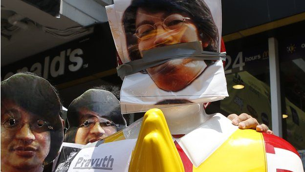 Thai protesters wear masks of Sombat Boonngamanong, next to a statue of Ronald McDonald during a rally at a shopping district in central Bangkok on 25 May, 2014