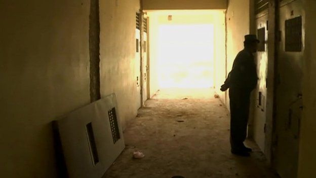 A guard inspects one of the derelict cells at Baghlan prison