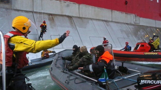 A Russian coast guard officer approaches Greenpeace activists attempting to climb the Prirazlomnaya oil platform in September 2013