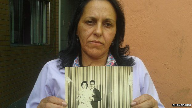 Taxi driver Maria Cecilia shows a wedding photo of her father, buried as pauper in Perus Cemetery