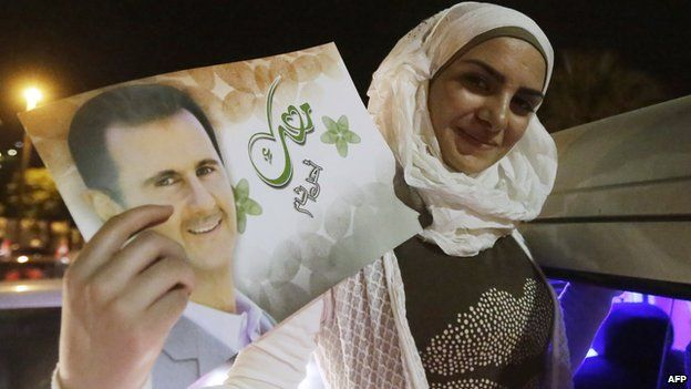 """A woman holds a picture of re-elected Syrian President Bashar al-Assad as she celebrates in Damascus after he was announced as the winner of the country""""s presidential elections on June 4"""