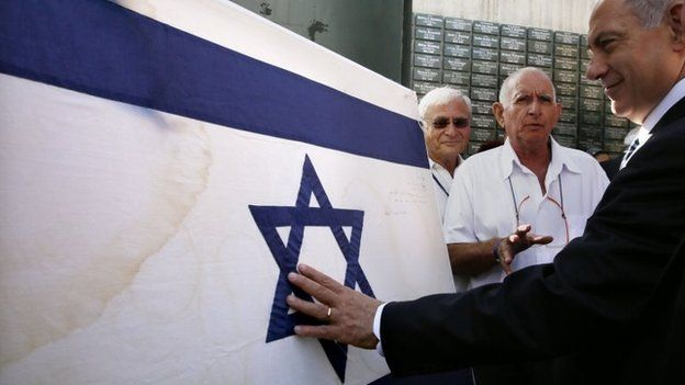 Israeli Prime Minister Benjamin Netanyahu touches the original flag Israeli paratroopers waved at the Western Wall in the 1967 Six Day War prior to a special Jerusalem Day Cabinet Meeting at Ammunition Hill on May 28