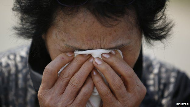 A relative of a victim onboard sunken passenger ship Sewol cries after paying tribute at the official memorial altar in Ansan on 2 May, 2014
