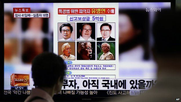 A woman watches a TV news programme on the reward poster of Yoo Byung-eun at the Seoul Train Station in Seoul, South Korea, on Monday, 26 May, 2014