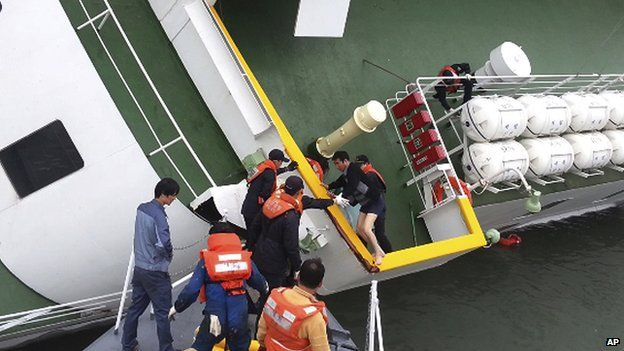 In this file photo taken on 16 April, 2014, South Korean coast guard officers rescue ferry Sewol captain Lee Joon-seok, wearing a sweater and underwear, from the ferry in the water off the southern coast near Jindo, South Korea