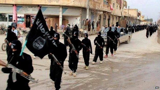 File image posted on a militant website in January 2014 shows fighters from the Islamic State of Iraq and the Levant marching in Raqqa, Syria