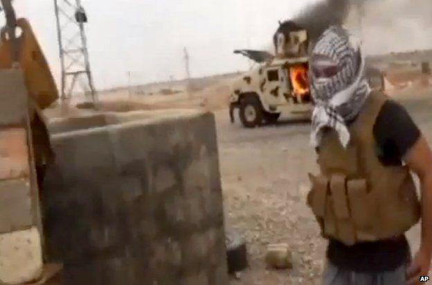 An Islamist fighter near a burning Iraqi army Humvee in Tikrit, 12 June