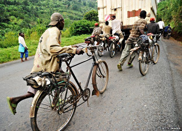 Burundian bicycle transporters run in Bujumbura to reach the back of a truck to hold onto to take an almost effortless ride up the mountain