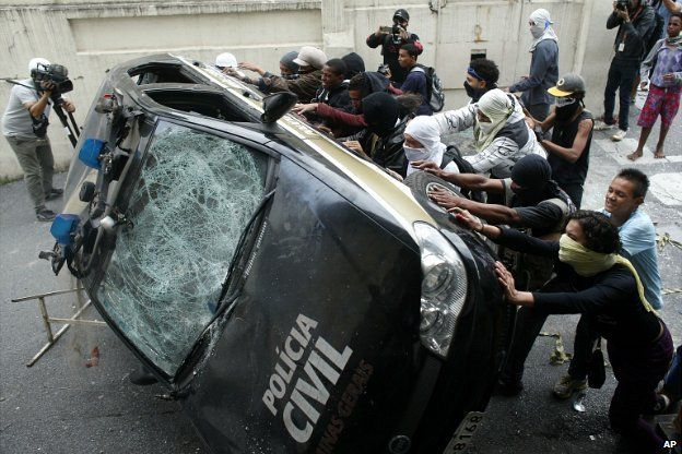 Demonstrators push over a police car during a protest in Belo Horizonte, Brazil - 12 June, 2014