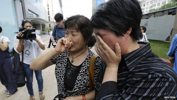 A woman (L), whose son, daughter-in-law and grandson were aboard the missing Malaysia Airlines flight MH370, cries in Beijing June 11