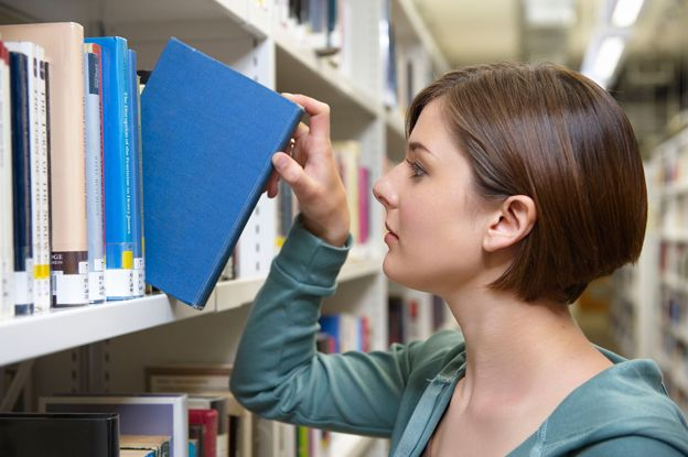 Woman takes book out of stack in library shelf