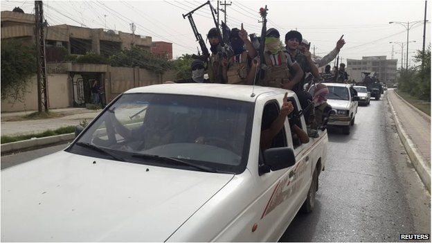ISIS fighters celebrate on vehicles taken from Iraqi security forces, at a street in city of Mosul on 12 June