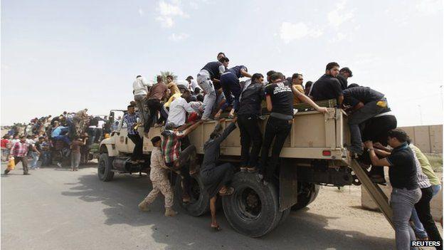 Volunteers board army trucks in Baghdad, on 13 June.