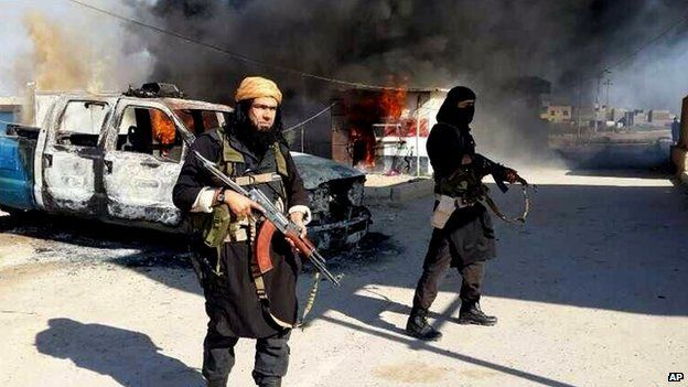 ISIS militants stand in front of a burning truck in Iraq.
