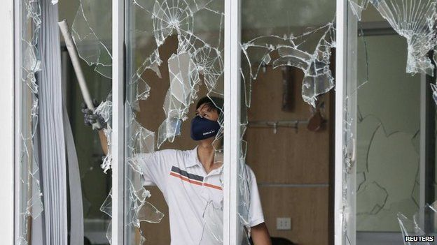 A man clears broken windows at the office of a Taiwanese company attacked in anti-China protests in Vietnam