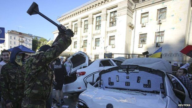 A protester smashes a car during a rally near the Russian embassy in Kiev - 14 June 2014