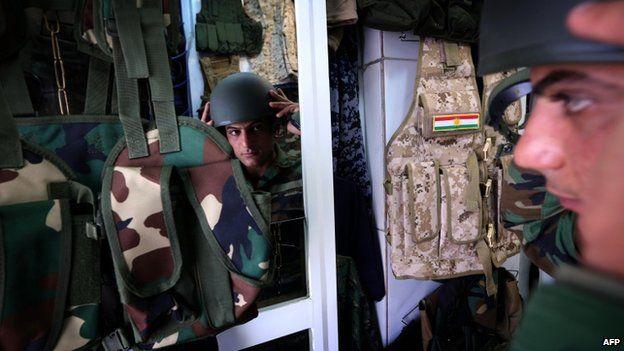 An Iraqi man tries on a military uniform in a shop in Irbil (16 June 2014)