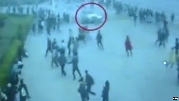 This screen grab taken from state broadcaster China Central Television (CCTV) footage on 16 June 2014 shows security camera footage of a white vehicle (top centre) driving along the pavement in a crash on 28 October 2013 in Beijing's Tiananmen Square that killed two tourists and wounded 40 others