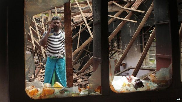 A Sri Lankan Muslim man talks over his mobile phone as he stands among the debris of his charred house, in Aluthgama, town, 50 kilometres (31 miles) south of Colombo, Sri Lanka, Monday, June 16, 2014.