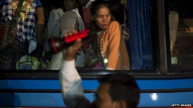 A Cambodia woman waits to get off a bus after crossing the Thai border on June 17, 2014 in Poipet