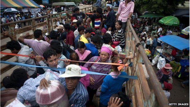 Cambodian workers wait inside a truck to take them to their home after crossing the Thai border on June 17, 2014 in Poipet