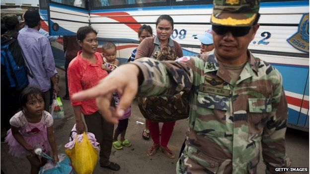 A Cambodian soldier helps workers after they cross the Thai border on June 17, 2014 in Poipet