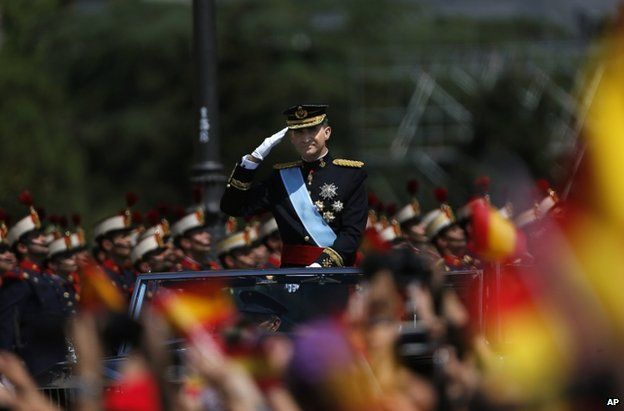 King Felipe salutes to the crowd as he rides in an open-top Rolls Royce during his arrival at the Royal Palace in Madrid, Spain, 19 June