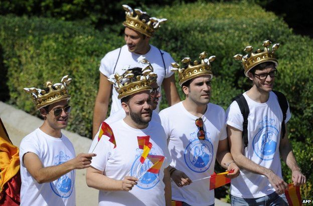Men in carnival crowns near the royal palace in Madrid, 19 June