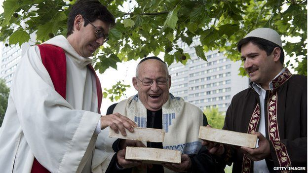 German Pastor Gregor Hohberg, Israeli Rabbi Tovia Ben-Chorin and German-Turkish Imam Kadir Sanci hold three bricks